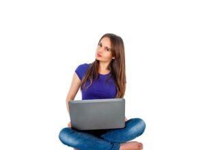 あぐらをかいてノートパソコンを使っている女性